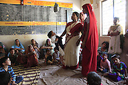 Two government healthcare workers (wearing distinctive red and white saris) weigh children in an Anganwadi clinic in Badnavar, western Madhya Pradesh. Paper-based records are kept, tracking the weight of all children up to the age of 5 - but keeping track of children can be difficult in tribal areas, where people often move from village to village in search of seasonal work.
