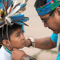 Anshekwe dance group member Lyndon Gasper helps Deandre Malikan secure a feather headpiece before the night parade in Zuni Thursday.