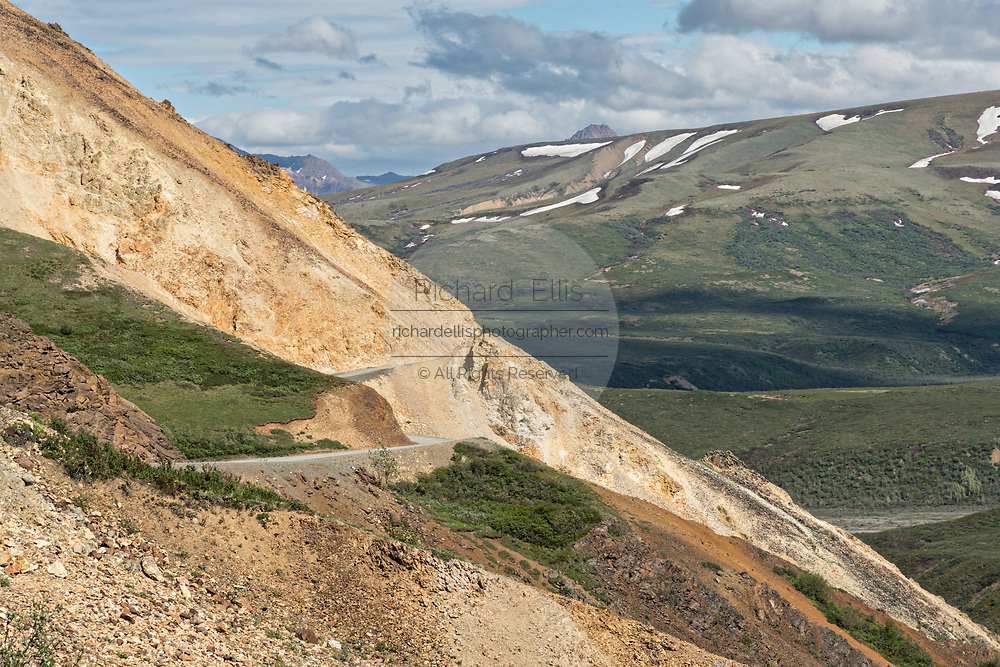 The Park Road clings to the side of the cliffs as it passes through Sable Pass near the Polychrome Hills in Denali National Park Alaska. Denali National Park and Preserve encompasses 6 million acres of Alaska's interior wilderness.
