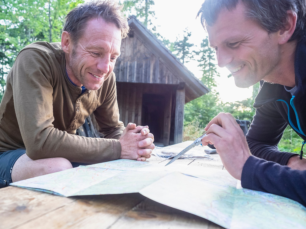 Two male hikers reading map while relaxing in front of small hut in Black Forest, Baden-Wuerttemerg, Germany
