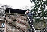 Nederland, Ubbergen, 19-3-2013Een schoorsteenveger, Jeroen de Haan, veegt het rookkanaal van de houtkachel.Foto: Flip Franssen/Hollandse Hoogte.