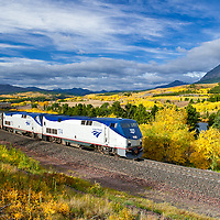 amtrak train approaching east glacier park montana, fall leaves summit little dog mountains back ground