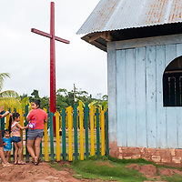 Local women stand by the colorful fence of the church in the small community of San Francisco de Loreto on the Marañon River in the Peruvian Amazon.