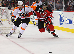 Jan 21; Newark, NJ, USA; New Jersey Devils defenseman Bryce Salvador (24) and Philadelphia Flyers center Sean Couturier (14) race for the puck during the second period at the Prudential Center.
