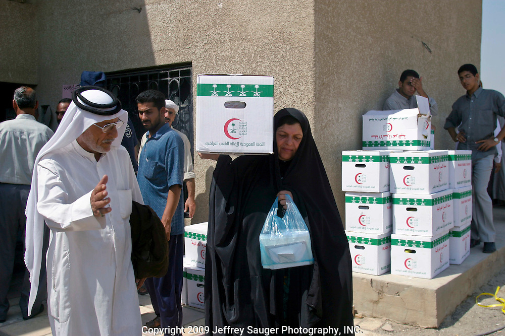A woman carries an emergency aid package she just received from the Community of Leaders and Chiefs for Iraqi Tribes in Baghdad, Iraq, Thursday, August 7, 2003. For many Iraqis, the community is the only place they can go to receive dependable aid. The community receives the aid packages from Saudi Arabia.
