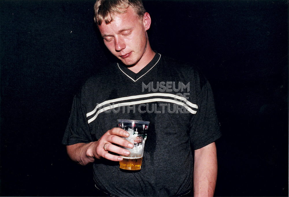 Young man standing with eyes closed and pint of beer in hand.