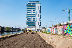 View of original section of Berlin Wall and controversial new construction site of apartment building beside River Spree at East Side Gallery in Friedrichshain, Berlin, Germany. Construction of new apartment buildings beside Berlin Wall means sections of wall are removed and construction is inside former public space beside River Spree.