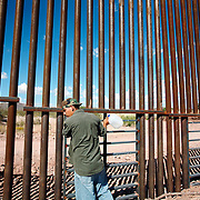 In the desert of Mexico, a man studies the border fence built on the Mexico/US boundary near Agua Prieta Mexico and Douglas, Arizona. The newly built fence is part of the project to secure the nearly 2,000 mile border - which is widely considered the most frequently traveled international border in the world, with an estimated 250 legal and 500 million illegal crossings every year. The man did not attempt to cross.