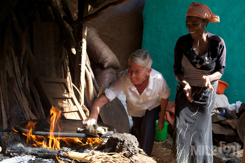 VSO volunteer Pat Gilhooley learning how to make injera on an open fire in her compound where she lives with an Ethiopian family. Injera is a large sourdough flatbread which is extremely popular and accompanies most meals in Ethiopia.