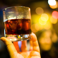 Hand holding a glass with alcoholic beverage, Seville, Spain