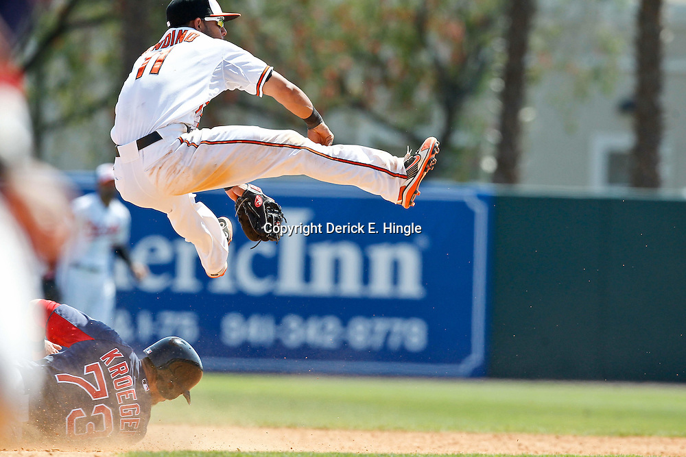 March 23, 2012; Sarasota, FL, USA; Baltimore Orioles shortstop Robert Andino (11) turns a double play as he leaps over a sliding Boston Red Sox right fielder Josh Kroeger (73) during the top of the fifth inning of a spring training game at Ed Smith Stadium.  Mandatory Credit: Derick E. Hingle-US PRESSWIRE