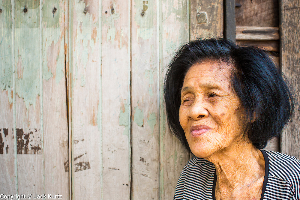 "10 JANUARY 2013 - BANGKOK, THAILAND: A Buddhist woman in front of her home in the Baan Krua neighborhood in Bangkok. The Ban Krua neighborhood of Bangkok is the oldest Muslim community in Bangkok. Ban Krua was originally settled by Cham Muslims from Cambodia and Vietnam who fought on the side of the Thai King Rama I. They were given a royal grant of land east of what was then the Thai capitol at the end of the 18th century in return for their military service. The Cham Muslims were originally weavers and what is known as ""Thai Silk"" was developed by the people in Ban Krua. Several families in the neighborhood still weave in their homes.   PHOTO BY JACK KURTZ"