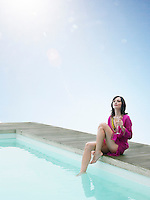 Woman with champagne dipping foot in outdoor pool