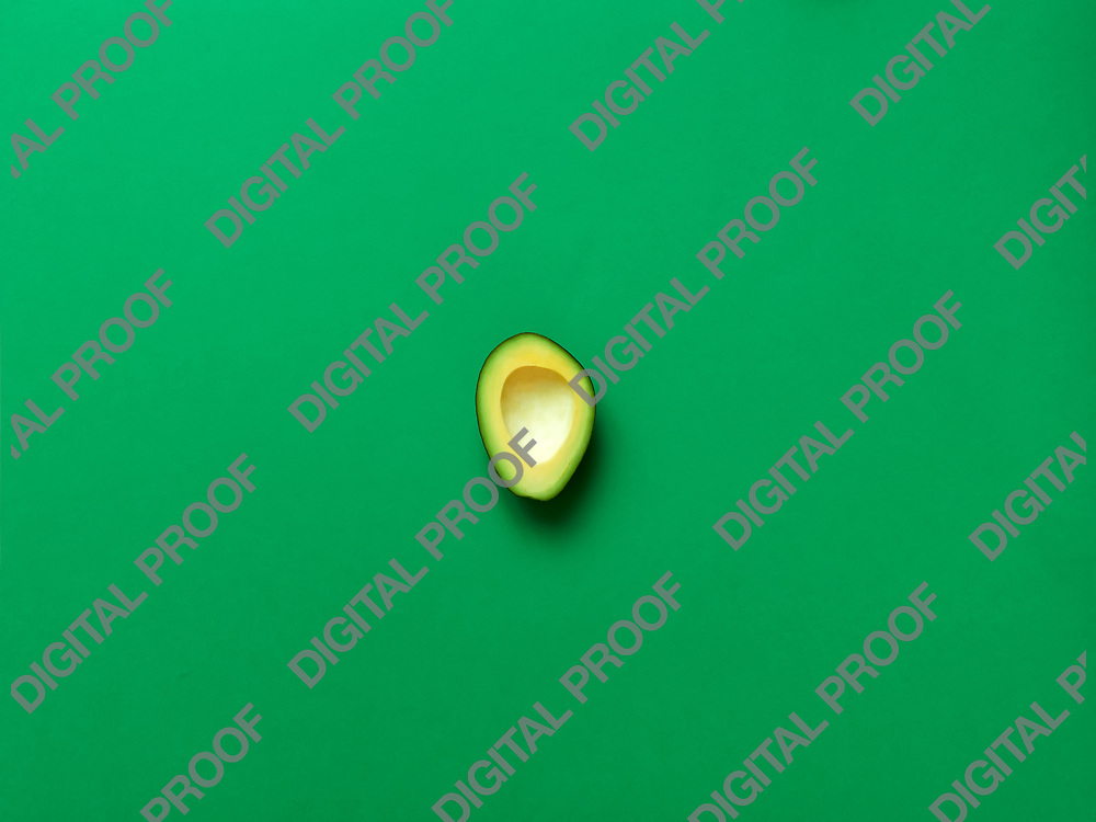 Avocado without seed isolated in green background viewed from above - flatlay look