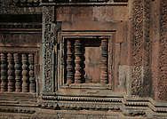This sandstone wall is from Banteay Srei (Citadel of Women), a richly decorated 10th century Cambodian temple dedicated to the Hindu god Shiva located in the Angkor Wat temple complex in Siem Reap, Cambodia. <br /> <br /> Banteay Srei has a central structure surrounded by a moat and an additional 3 enclosures. It was built in hard red sandstone that is adorned in spectacular bas-reliefs and elaborate decorative wall carvings. <br /> <br /> Quite a few of the temples at Angkor have been restored and represent the most magnificent site of Khmer architecture including the world's largest single religious monument,  the breathtaking Angkor Wat.<br />  <br /> Containing some of the finest examples of classical Khmer art, the walls of  Banteay Srey are densely covered with some of the most beautiful, deep and intricate carvings of any Angkorian temple. <br /> <br /> From the pink sandstone to the ornate design that includes many amazing devatas, it is a dreamy setting and an experience unto itself.