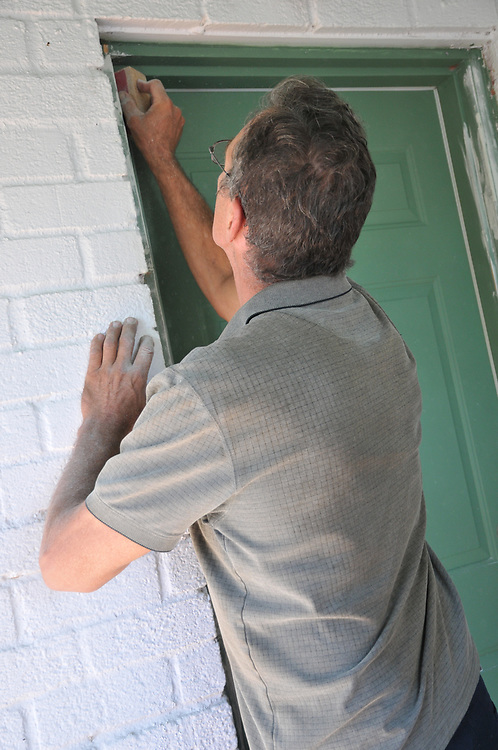 After replacing the hinges and repainting and rehanging my back door, Hugh Goglin turns his attention to sanding areas where he repaired the door frame.