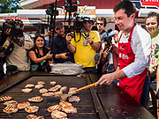 13 AUGUST 2019 - DES MOINES, IOWA: PETE BUTTIGIEG flips pork chops and pork burgers at the Iowa State Fair. Buttigieg, the Mayor of South Bend, Indiana, is running to be the Democratic nominee for the US presidency. He spoke at the Des Moines Register Political Soap Box at the Iowa State Fair and then toured the fairgrounds. Iowa has the first event of the presidential selection cycle. The Iowa Caucuses are February 3, 2020.              PHOTO BY JACK KURTZ