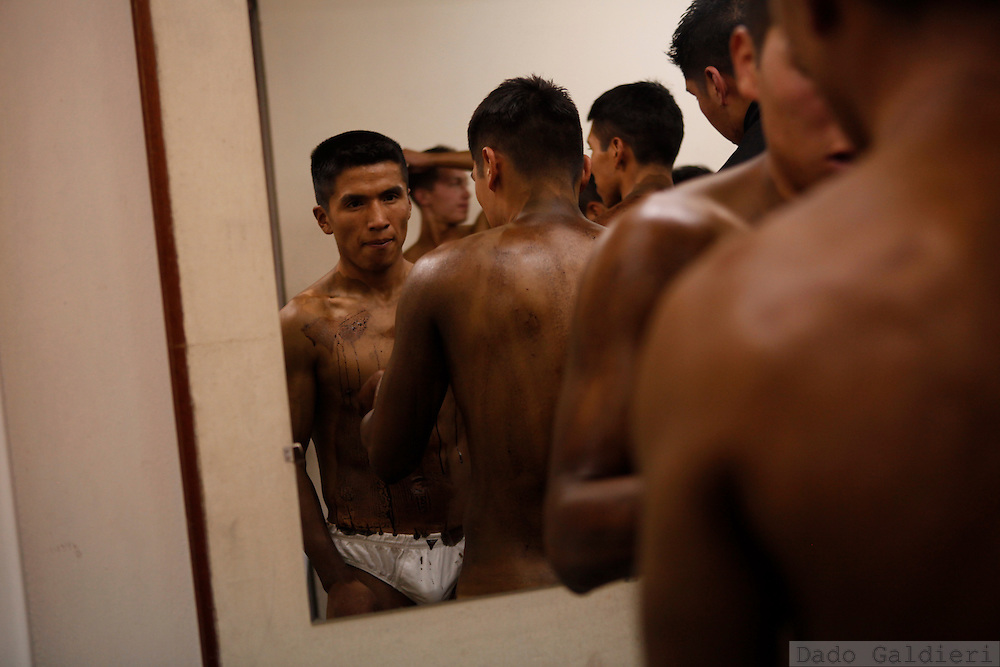 Bodybuilders apply makeup to their bodies before competing in a regional bodybuilding championship in La Paz, Saturday, April 10, 2010.
