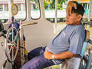 21 NOVEMBER 2012 - BANGKOK, THAILAND: A ferry captain relaxes before crossing the Chao Phraya River. A network of ferries connect the Thonburi section of Bangkok to Bangkok proper, crossing the Chao Phraya River. The fare is 3 Thai Baht, about $ 0.15 (US). The boats are the fastest way to get from north to south in Bangkok. Thousands of people commute to work daily on the Chao Phraya Express Boats and fast boats that ply Khlong Saen Saeb. Boats are used to haul commodities through the city to deep water ports for export.    PHOTO BY JACK KURTZ