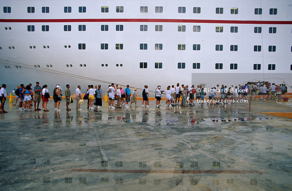 Largely American passengers re-join their cruise holiday voyage around the Gulf of Mexico during a day's stop-over in Cancun, Mexico. Reflected in the puddles of recent seasonal rain, they queue up on the port's quayside to have their identity passes checked before being allowed back on board the Fun Ship Ecstasy. Seen above them and in reflected in the water at their feet are some of the many windows and portholes of this enormous vessel belonging to the Vegas-style Carnival Cruise lines company. The Panamanian-registered MS Ecstasy is a 70,367 ton cruise ship carrying 2,052 passengers and 920 crew whose routes are mainly around the Gulf and Carribean Sea.
