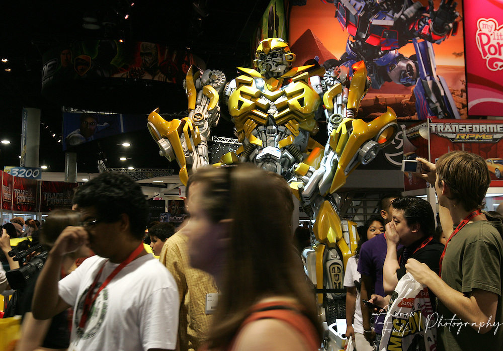 "/Andrew Foulk/ For The North County Times/.Comic Con attendees walk past a life size model of ""Bumble Bee"" from the Transformers movie , during preview night at the 40th annual San Diego Comic Con International."