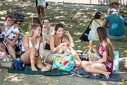 © Licensed to London News Pictures. 07/08/2020. London, UK. Friends enjoy a cooling drink in the shade next to the River Thames at Richmond in South West London as temperatures are expected to reach to 35c today. Thousands of sun seekers have flocked to parks, rivers and the south coast as temperatures soar with beaches and roads becoming jammed with holidaymakers. The heat is set to continue for the rest of the week with temperatures expected in the high 20s. Photo credit: Alex Lentati/LNP