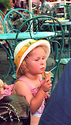 Girl age 4 eating ice cream cone in sidewalk cafe.  Warsaw Poland