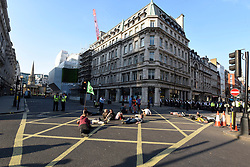 "© Licensed to London News Pictures. 19/04/2019. LONDON, UK.  Activists lie in the road in Regent Street to block the path of the pink boat being towed away from Oxford Circus during ""London: International Rebellion"", on day five of a protest organised by Extinction Rebellion.  Protesters are demanding that governments take action against climate change.  Police have issued a section 14 order requiring protesters to convene at Marble Arch only so that the protest can continue.  Photo credit: Stephen Chung/LNP"