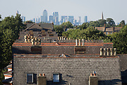 The rooftops of Sydenham houses and in the distance, the tall buildings of London Docklands, on 23rd July 2018, in London, England.