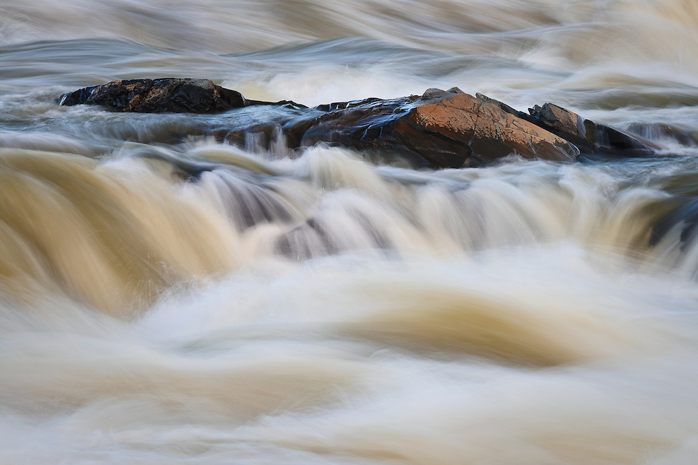Abstract of the swollen and silt-ladden Potomac River flowing past rocks just above the Great Falls in January, Great Falls National Park, Great Falls, Virginia