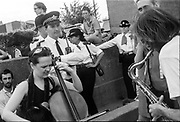 Saxophonist and cellist play near police officers, Reclaim the Streets, Shepherd's Bush, London, July 1996