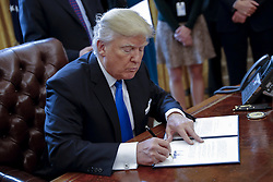 January 24, 2017 - Washington, District of Columbia, United States of America - US President Donald Trump signs one of five executive orders related to the oil pipeline industry in the oval office of the White House in Washington, DC, USA, 24 January 2017. President Trump has a full day of meetings including one with Senate Majority Leader Mitch McConnell and another with the full Senate leadership..Credit: Shawn Thew / Pool via CNP (Credit Image: © Shawn Thew/CNP via ZUMA Wire)