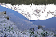 Mount Rainier reflects in partially frozen Reflection Lake and vegetation on the shore with a heavy hoarfrost in autumn.