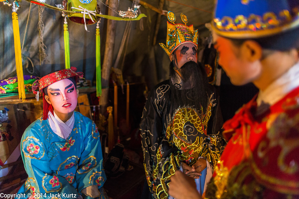 "28 JANUARY 2014 - BANGKOK, THAILAND: Performers with the Tear Kia Ee Lye Heng opera troupe relax backstage during a show. They were performing for a business in the Min Buri district of Bangkok for the Lunar New Year, which this year is Jan 31. Chinese opera was once very popular in Thailand, where it is called ""Ngiew."" It is usually performed in the Teochew language. Millions of Teochew speaking Chinese emigrated to Thailand (then Siam) in the 18th and 19th centuries and brought their cultural practices with them. Recently the popularity of ngiew has faded as people turn to performances of opera on DVD or movies. There are still as many 30 Chinese opera troupes left in Bangkok and its environs. They are especially busy during Chinese New Year when they travel from Chinese temple to Chinese temple performing on stages they put up in streets near the temple, sometimes sleeping on hammocks they sling under their stage. They are also frequently hired by Chinese owned businesses to perform as a form of merit making.    PHOTO BY JACK KURTZ"