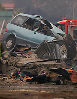 A damaged car amongst fallen debris in the City Centre after a Powerful earth quack ripped through Christchurch, New Zealand on Tuesday lunch time killing at least 65 people as it brought down buildings, buckled roads and damaged churches and the Cities Cathedral. Photo Tim Clayton