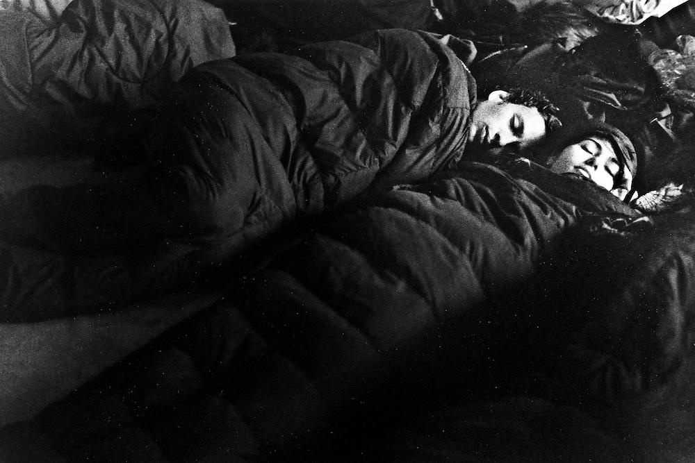 Genova, venerdì 20 luglio 2001. Giornata delle piazze tematiche. Prima del corteo della disobbedienza civile, una coppia di manifestanti dorme nei sacchi a pelo allo stadio Carlini.