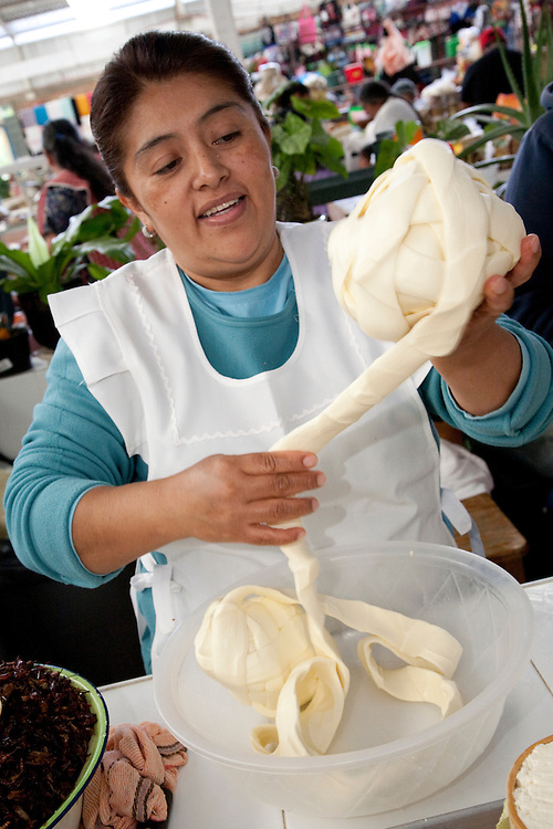 North America, Mexico, Oaxaca Province, Etla, woman rolling string cheese for sale in market