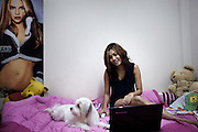 YANGON,MYANMAR,MARCH 2012: Ha Moon in her bedroom replying to fan's emails.<br /> Burma is a country in Transition. And if that hasn't been made clear enough by the political debates and the recent by-elections, meet the Me N Ma Girls, the first girlband in the country.<br /> The timing couldn't be better. After the April 1st elections in 2012 an always increasing number of investors from all over the world has been visiting Myanmar. After decades of military regime and isolation, the strings of censorship have started loosening up. The government censors in fact for years have banned songs and articles, deleting anything that was seen as &quot;to provocative&quot; such as leather outfits and colored wigs.<br /> Describing themselves as Myanmar's first all-girl group, under the management of the Australian dancer and choreographer Nicole May, these five women - coming from either Buddhist or Catholic background and formerly known as Tiger Girls - not only have been challenging censorship laws but they're as well trying to win hearts in a society that in many ways remains man-dominated and socially conservative.<br /> In a country that has been locked up for years, the Me N Ma Girls, embracing western pop culture with skimpy outfits and catchy songs, show with every performance the will of the Burmese youth to come out of a decades-long isolation.<br /> Five girls leading a new form of rebellion: the kind that questions roles and cultural norms.