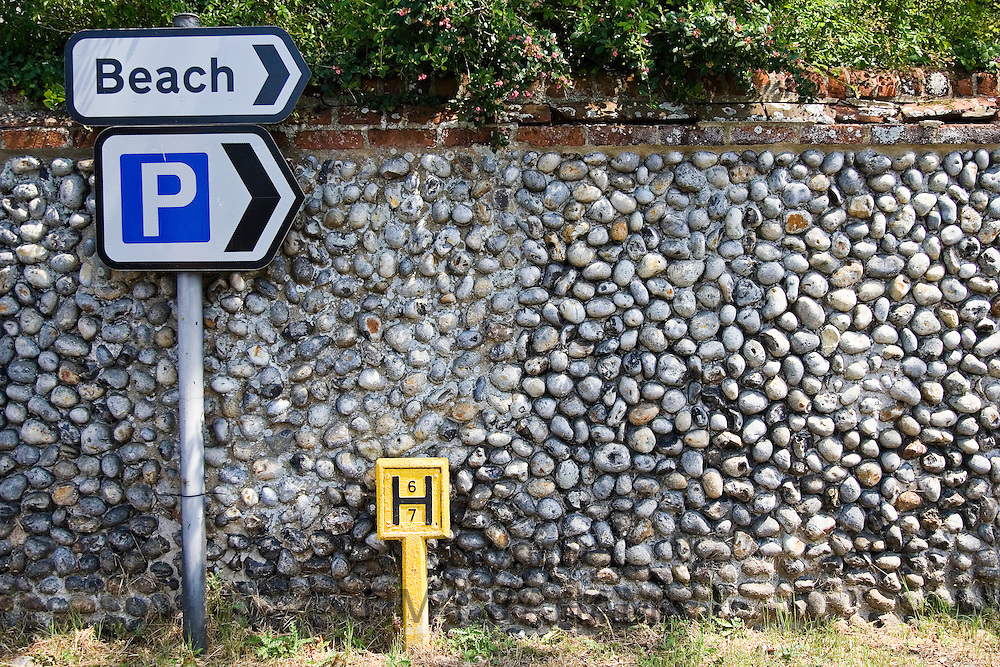 Parking and To the Beach signposts and fire hydrant by brick and flint wall, Happisburgh, Norfolk, UK