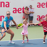 August 16, 2014, New Haven, CT:<br /> Sam Stosur leads a chain of kids as she hits a forehand during a tennis clinic in the AETNA FitZone as part of Kids Day on day three of the 2014 Connecticut Open at the Yale University Tennis Center in New Haven, Connecticut Sunday, August 17, 2014.<br /> (Photo by Billie Weiss/Connecticut Open)