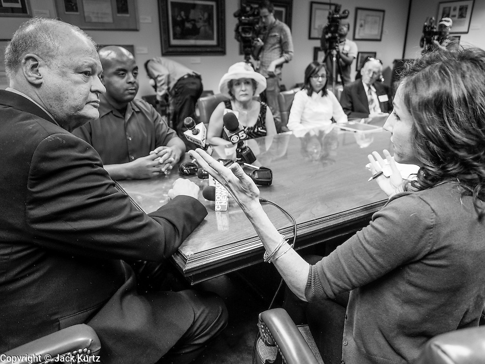 21 OCTOBER 2013 - PHOENIX, AZ: Arizona Attorney General TOM HORNE (left) and DREAM Act protester MOLLY DURAN argue about a decision by Horne at a meeting with DREAM Act protesters. The DREAMers are protesting the decision by Attorney General Horne to sue the Maricopa County Community College District to force the district to charge in-state tuition to the young people who qualify for the federal government deferred-action program.     PHOTO BY JACK KURTZ