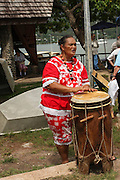 Woman with traditional drum welcomes guests, French Polynesia, Marquesas Islands, Nuku Hiva