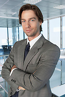 Business man with arms crossed in office building portrait