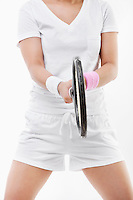 Midsection of young sportswoman holding tennis racket over white background