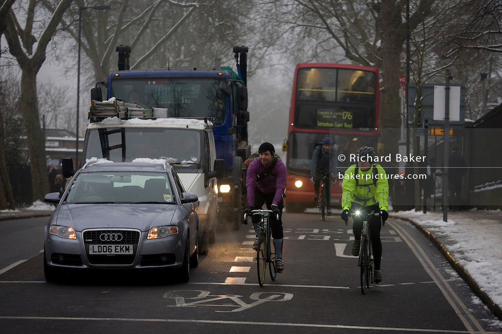 Drivers and cyclists share two lanes of a road junction in freezing mid-winter temperatures. Commuters are stopped at lights near Denmark Hill during a prolonged cold spell of bad weather when snow fell continuously on the capital days before in the borough of Lambeth.