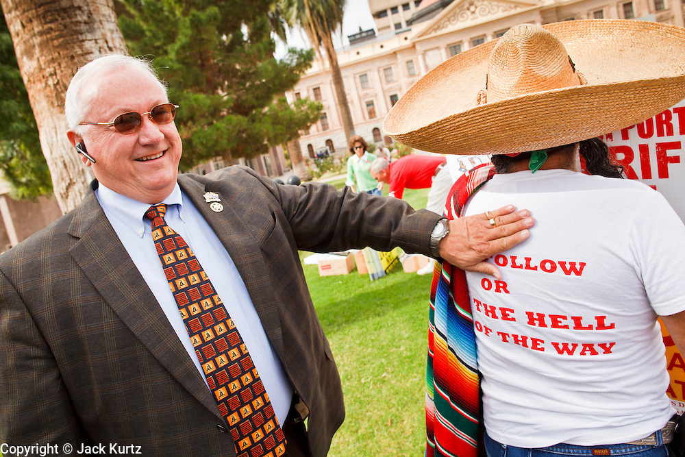 22 OCTOBER 2010 - PHOENIX, AZ:  Arizona State Senator RUSSELL PEARCE, a Republican and Tea Party supporter, jokes with ARTHUR OLIVAS, a legal Mexican immigrant and naturalized US citizen before a Tea Party rally in Phoenix. Pearce is a staunch opponent of illegal immigration and the author of SB 1070, Arizona's tough anti-illegal immigration bill. About 300 people attended a Tea Party rally on the lawn of the Arizona State Capitol in Phoenix Friday. They demanded lower taxes, less government spending, repeal of the health care reform bill, and strengthening of the US side of the US - Mexican border. They listened to Arizona politicians and applauded wildly when former Alaska Governor Sarah Palin and her son, Trig, made a surprise appearance. The event was a part of the Tea Party Express bus tour that is crossing the United States.     Photo by Jack Kurtz