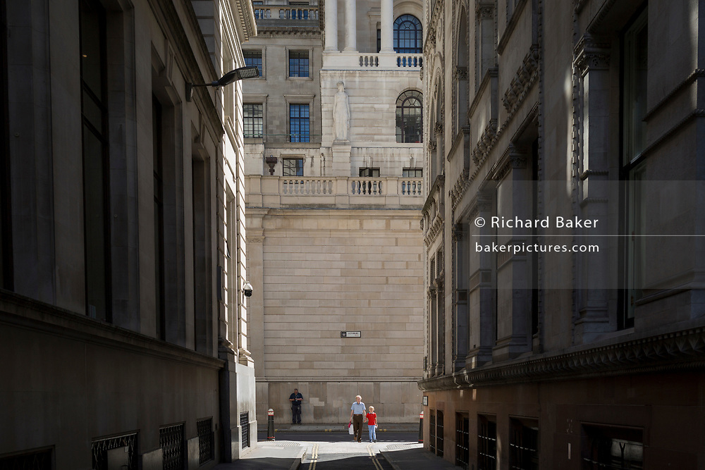 People walk beneath the high walls outside the Bank of England during the 2018 heatwave in the City of London, the capital's historic financial district, on 2nd August 2018, in London, England.