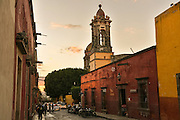 People stroll down Canal Street toward the Las Monjas church at sunset in the colonial UNESCO world heritage town of San Miguel de Allende, Mexico.
