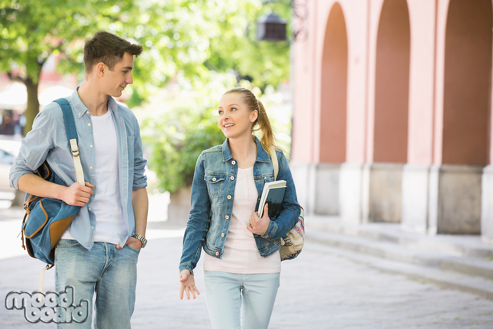 Young college friends talking while walking at campus