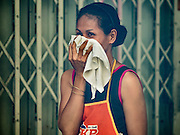 02 DECEMBER 2015 - BANGKOK, THAILAND:   A woman covers her face as chemicals used to fog her neighborhood and kill mosquitoes to prevent the spread of dengue fever linger in the air. The Public Health Ministry in Thailand said that more than 111,000 cases of dengue fever have been reported in 2015, an increase of more than 200% over the number of cases of dengue fever reported 2014. Dengue fever is a virus spread by mosquito and is endemic in southeast Asia. Thai health officials are aggressively spraying areas where mosquitoes are known to live and leading public information and education sessions on preventing dengue fever. There is no vaccine for dengue fever, so preventing dengue means avoiding mosquitoes.      PHOTO BY JACK KURTZ